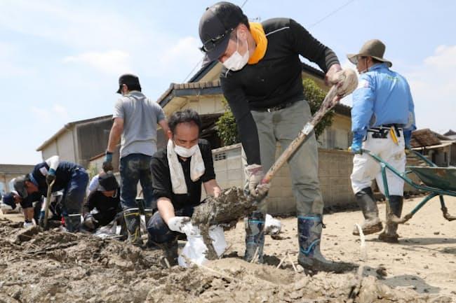 西日本豪雨の被災地で土のうを作るボランティア(7月14日、岡山県倉敷市真備町地区)