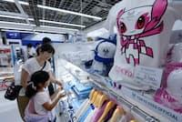 東京2020オフィシャルショップでマスコット入りの公式グッズを買い求める親子(東京都新宿区)
