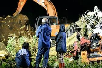 安否不明の親族の捜索活動を見守る人たち(7日、北海道厚真町)