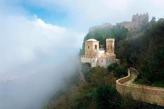 イタリア、エリチェ: 夢の世界のような山頂の景色を見るには、ケーブルカーが便利。地元では、中世風の建物が雲海に浮かぶ姿を「ビーナスのキス」とも呼んでいる。もともと異教徒の礼拝所だった村は、シチリア職人の伝統に忠実で、工房では手塗りの陶器や手織りじゅうたんなどが売られている(PHOTOGRAPH BY VISIONS FROM EARTH, ALAMY STOCK PHOTO)