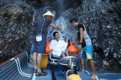 バリアフリーツアーで滝行を体験する参加者(石川県中能登町)
