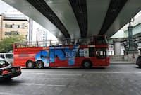 日本橋を通る観光バス。首都高の高架が頭上の青空を遮る(東京都中央区)