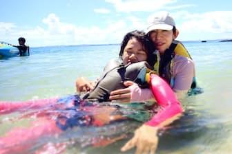 沖縄の海で、親子でリハビリをする杉本親子