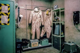 つるされたままになっているのは、有害なジェット燃料からタイタンIIミサイルの技術者を守る防護服だ(PHOTOGRAPH BY ADAM REYNOLDS)