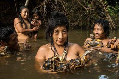ブラジル、アマゾンの先住民アワの女性たち。水浴びをしながらペットのカメを洗っている(PHOTOGRAPH BY CHARLIE HAMILTON JAMES, NATIONAL GEOGRAPHIC)