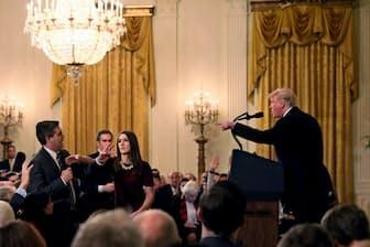 11月7日、米ホワイトハウスで記者会見するトランプ大統領(右)と、質問するCNNのジム・アコスタ記者(左端)=ロイター共同