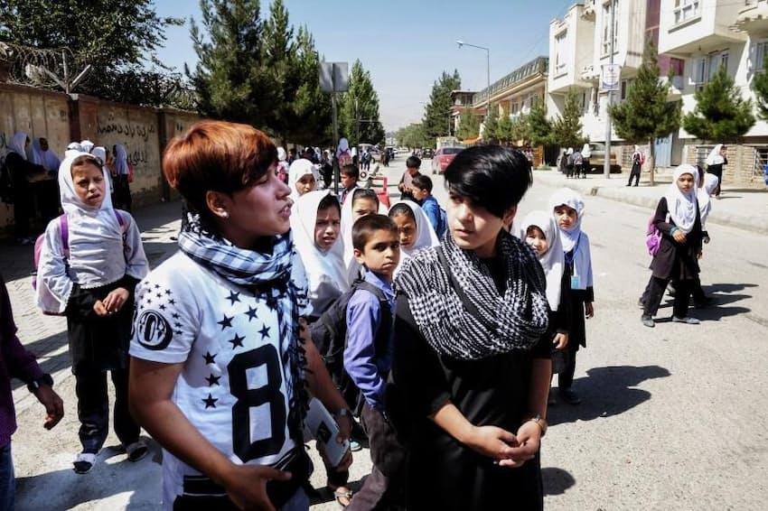 校門の外で、中傷したり服装をからかってくる子どもたちに言い返すセタールとアリの姉妹。「どうして男の子みたいな恰好をしているのかと聞かれることはしょっちゅうです」と、セタールは言う(PHOTOGRAPH BY LOULOU D'AKI, NATIONAL GEOGRAPHIC)