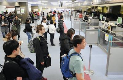 出国税は外国人だけでなく、日本人にも課税される(成田空港で入国審査を受ける外国人観光客ら)