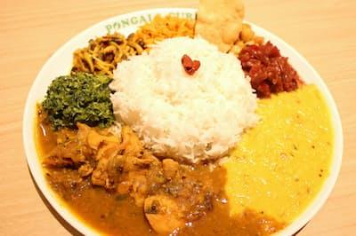「ポンガラカレー」の「スリランカプレート」。左下から時計回りに「スリランカチキン」「小松菜のマッルン」「しめじのモジュ」「ポルサンボル」「パパダム」「ひよこ豆のテンペラード」「ビーツのカレー」「レンズ豆のカレー」