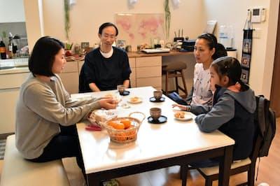 戸建て型の民泊施設で住人の山口さん(左端)と交流するタイ人一家(12月11日、東京都世田谷区)