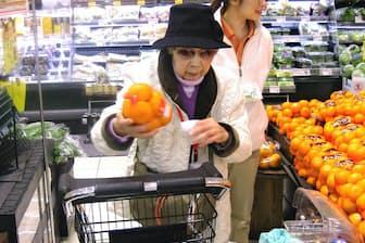 介護事業所の職員に付き添われながら買い物を楽しむ古市さん(左)(山形県天童市)
