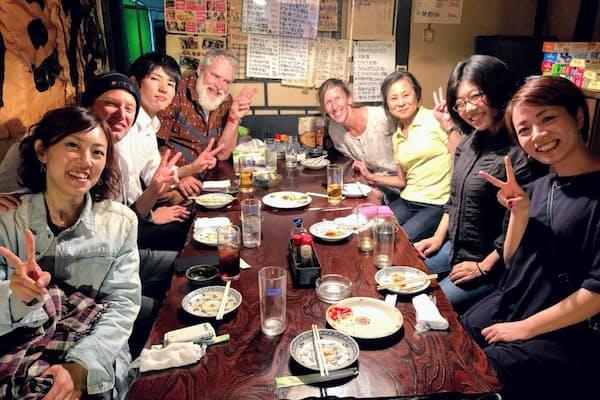 商店街の居酒屋で、地元の日本人客らと一緒にポーズをとる外国人観光客