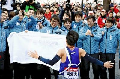 1位でゴールしたアンカーを迎える東海大のチームメート(東京・大手町)=共同