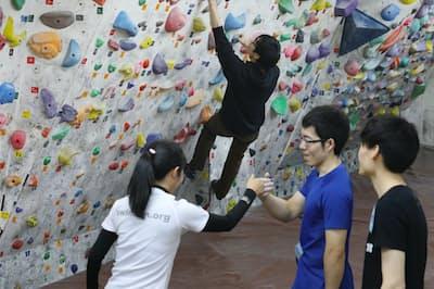 相手が登っている姿を見て、助言したり励まし合ったりする(都内で開かれたボルダリングの合コン)