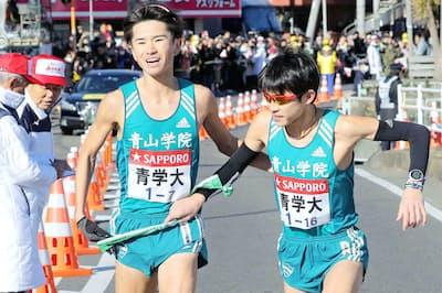 青山学院大は残念ながら5連覇を逃した。写真は平塚中継所で7区の林(左)からたすきを受け取る8区の飯田(代表撮影)=共同