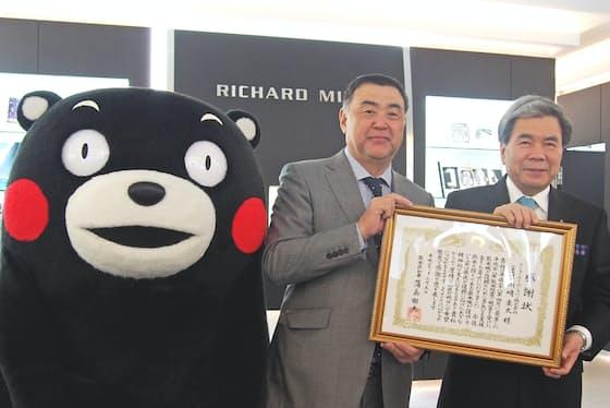 熊本県のPRキャラクター「くまモン」とリシャールミルジャパンの川崎社長、熊本県の蒲島知事(左から)