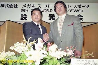SWS設立会見で握手する天龍氏とメガネスーパーの田中八郎社長(1990年5月10日、都内)=東京スポーツ新聞社提供