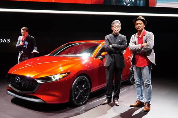 新型「マツダ3」こと「アクセラ」が2018年11月30日~12月9日まで米国で開催された「ロサンゼルスオートショー」で初公開された。マツダの常務執行役員デザイン・ブランドスタイル担当 前田育男氏(左)と小沢コージ氏