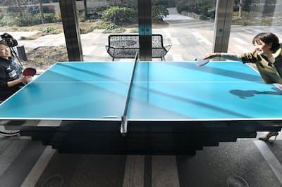 コートの片側が長い卓球台では、車いすに乗った選手の感覚を体験できる(1月、東京都港区)