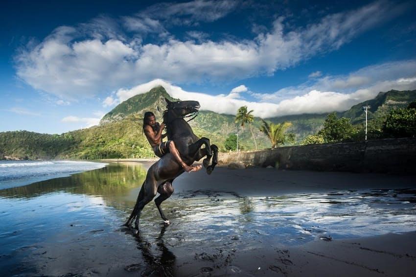 ヒバ・オア島の黒い砂浜で、馬と共に躍動するジェレミ・ケフエヒトゥ(PHOTOGRAPH BY JULIEN GIRARDOT)