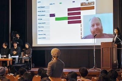 スクリーンに映る出展アーティストに入札内容を提示する参加者(横浜市中区)