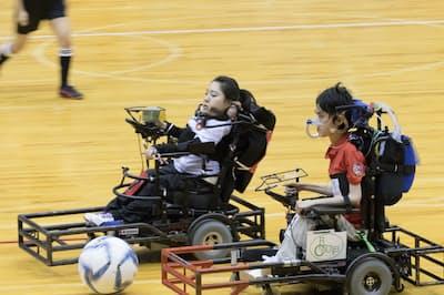 ボールを追って競り合う永岡真理(左)と東武範(2017年9月、日本電動車椅子サッカー選手権大会)=永岡一男提供