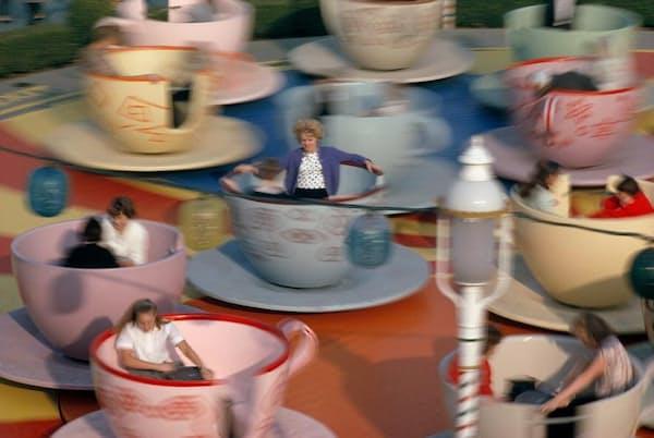 不思議の国のアリスのアトラクション「マッド・ハッターズ・ティー・パーティー」でティーカップに乗り、クルクル回る人々。開園50年目には、特別な金色のティーカップが用意された(PHOTOGRAPH BY THOMAS NEBBIA, NATIONAL GEOGRAPHIC CREATIVE)