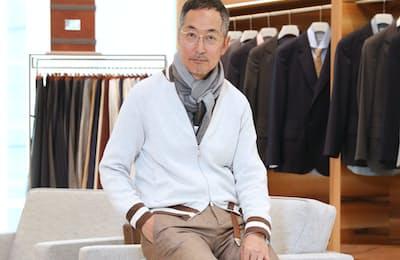 茶のスーツのジャケットを脱ぎ、ニットブルゾンとストール合わせた引野実さん。白を使うと顔立ちが一層映える