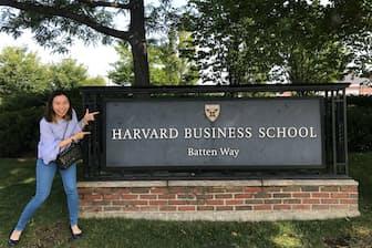 ハーバードビジネススクールの校標前でほほ笑むエイミー・アサワテワウィスさん