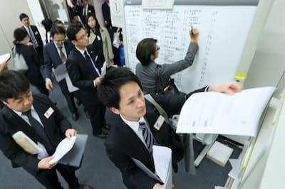 決算発表の資料を棚に入れる企業の担当者ら(東証)