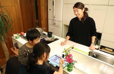 夕食の準備をしながら子どもたちの相手をする土佐礼子(松山市の自宅)