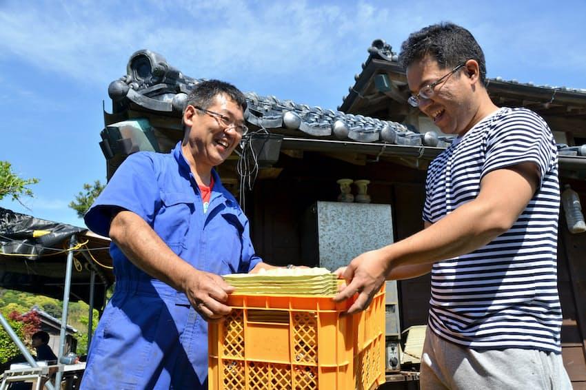 地元の養鶏業者から差し入れの卵を受け取る成田剛史さん(左)(千葉県南房総市)