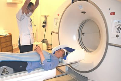 PET検査を前に姿勢の説明を受ける男性(4月、浜松市の浜松PET診断センターで)