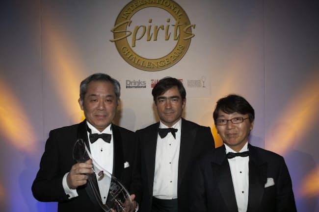 サントリースピリッツのウイスキーは相次いで世界的な受賞を果たした(トロフィーを持つ輿水氏、写真左)