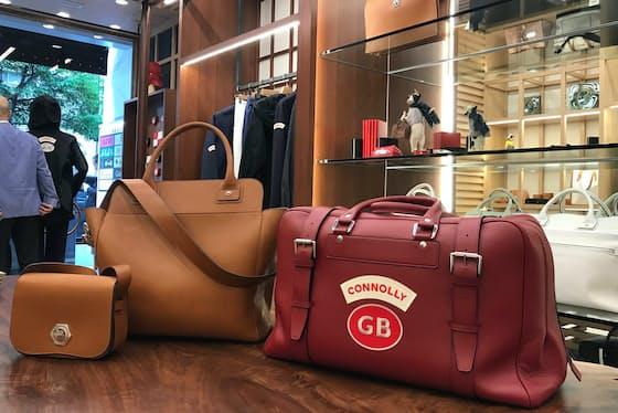 ワッペンが付いたトラベル用のバッグ(右)は車のシートレザーと同じ革を使っている(東京都中央区)