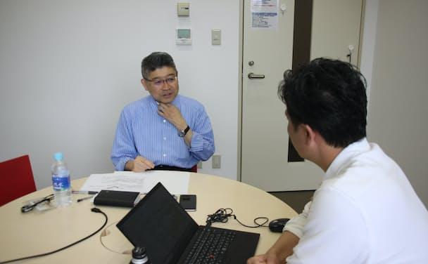 本社の課長からヒアリングを行う筆者(左)