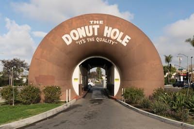 ラ・プエンテにあるドーナツ・ホールは店の両端に巨大なドーナツを配した建物で、ドライブスルーの車は2つのドーナツの下を通り抜けて注文する(PHOTOGRAPH BY THEO STROOMER)