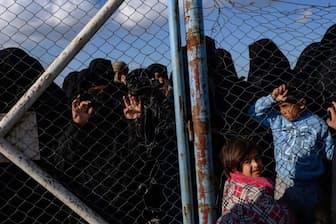 バグズからシリア北部のアルホル難民キャンプへ移送されてきた人々を、フェンスの向こうから眺める女性と子どもたち。彼女らはIS戦闘員の家族で、いまだにISを熱狂的に支持している(PHOTOGRAPH LYNSEY ADDARIO, NATIONAL GEOGRAPHIC)