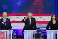 サンダース上院議員(中)は米民主党の大統領選候補者討論会で財政赤字容認論と明確に距離をとる主張をしていた(6月、米マイアミ)=ロイター