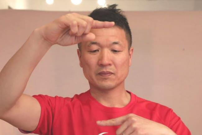 目だけをなるべく早く上下に動かして指を交互に見る。素早くできない場合は脳の処理機能が低下している可能性も…。(写真 鈴木愛子)