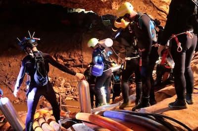 タムルアン洞窟の中でポンプを使って懸命に排水作業を行うタイの救助隊。モンスーンの影響で、巨大な洞窟の内部には大量の水が流れ込んでいた(AND PHOTOGRAPH BY ROYAL THAI NAVY/AP IMAGES)