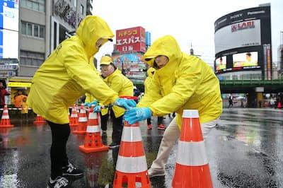東京マラソンのレース開始前、交通規制の準備をするボランティア(3月、東京都新宿区)