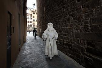 フィレンツェの狭い裏通りを歩くバルテー・コンティさん。1990年からレオナルド・ダ・ヴィンチの再現役者をやっている。言葉を発することなく匿名で演じられる再現役者が、自分には合っていると語る(PHOTOGRAPH BY PAOLO WOODS AND GABRIELE GALIMBERTI)