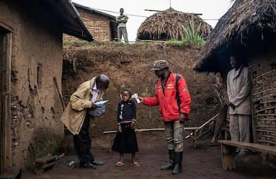 コンゴ北東部の村バヤナで、WHOのチームがコンフィルメ・マシカ・ムガニラちゃん(7)の体温を測る。彼女は、両親と兄、妹をエボラで亡くし、親戚に育てられている(Photograph by Nichole Sobecki)