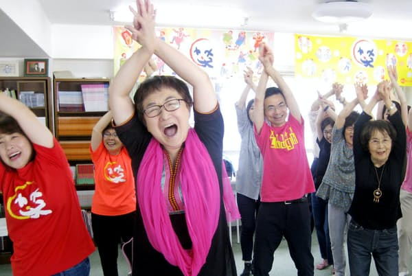 笑い声を出しながら、さまざまなポーズを取って体を動かす笑いヨガの参加者(東京都千代田区)