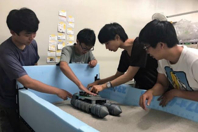 砂を敷き月面に模した場所を探査機が走行する実験を行う都立産技高専の学生たち
