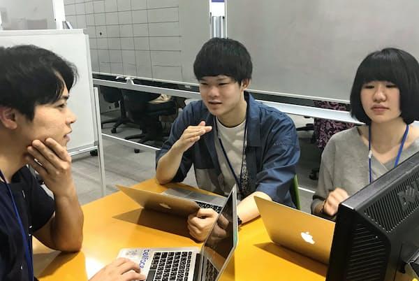 インターン中、社員(写真左)と相談する学生たち(東京都新宿区)
