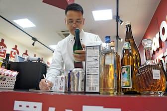 持ち込まれた酒を1本ずつ査定する(東京都品川区のリカーオフ武蔵小山パルム店)