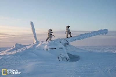 カナダ北部ヌナブト準州のコーンウォリス島で行われたサバイバル訓練中、カナダ兵が飛行機の残骸に上る。北極の温暖化に伴い、将来の覇権をめぐって緊張が高まるなか、カナダ軍と米軍は北極での活動を強化している(PHOTOGRAPH BY LOUIE PALU)