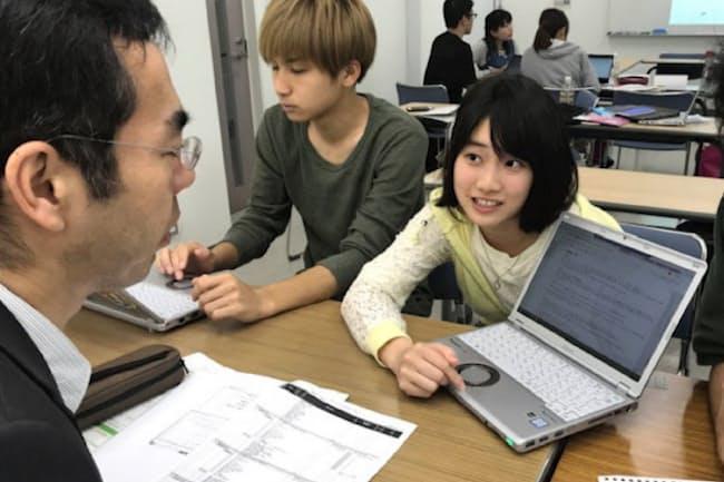 ゼミ生から分析の途中経過を聞く河本教授(左)